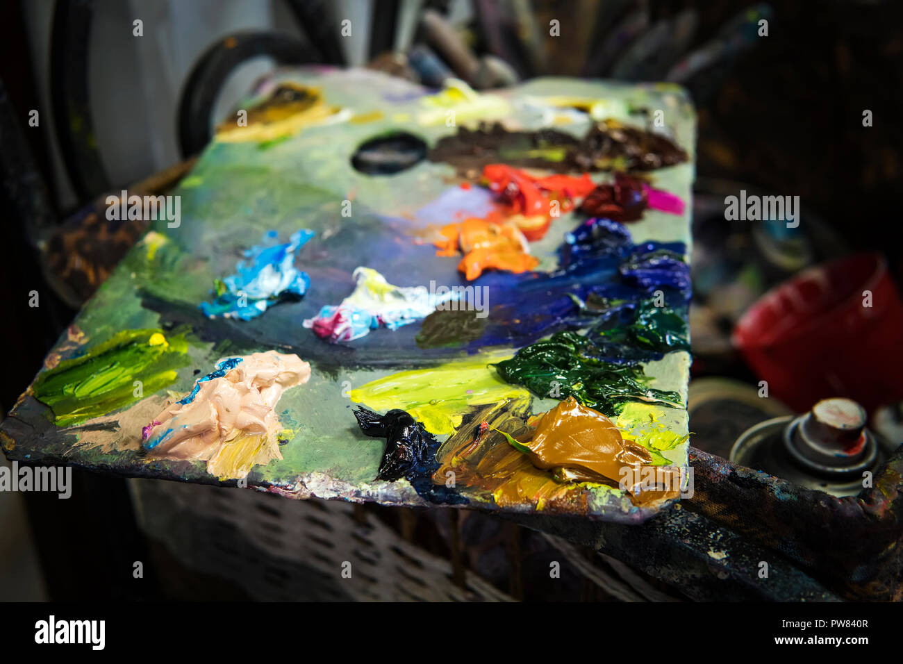 A close up of a varicoloured oil pallette in a painter workroom. An artist's palette consisting of diffrent oil paints. Oils spread over a colour pall - Stock Image