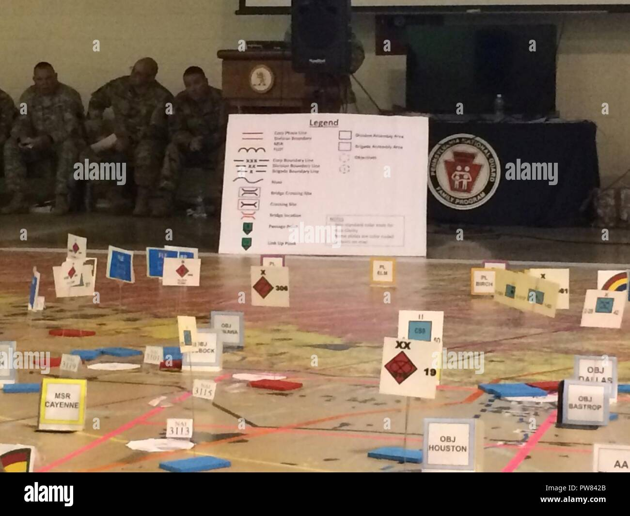Cardboard markets indicate enemy units and objectives on a giant map at Fort Indiantown Gap, Pennsylvania on Oct. 4, 2017, as leaders of the New York Army National Guard's 42nd Infantry Division conduct a Rehearsal of Concept exercise during their Warfighter exercise. Leaders move markers representing their units and discuss their actions at that phase of the battle to ensure that all leaders and staff understand the plan. ( U.S. Army National Guard - Stock Image