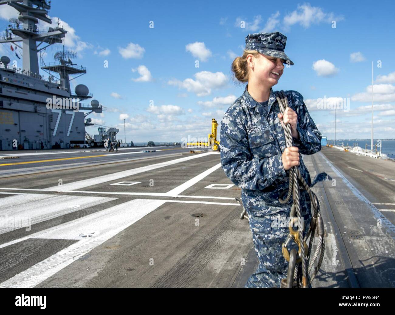 NORFOLK, Va (Oct. 2, 2017) Aviation Boatswain's Mate (Equipment) Sarah Dudrey walks an arresting gear cable across the flight deck of the aircraft carrier USS George H.W. Bush (CVN 77). The ship is in port Norfolk, Virginia, conducting routine maintenance after a seven-month deployment in support of maritime security operations and theater security cooperation efforts in the U.S. 5th and 6th Fleet areas of responsibility. Stock Photo