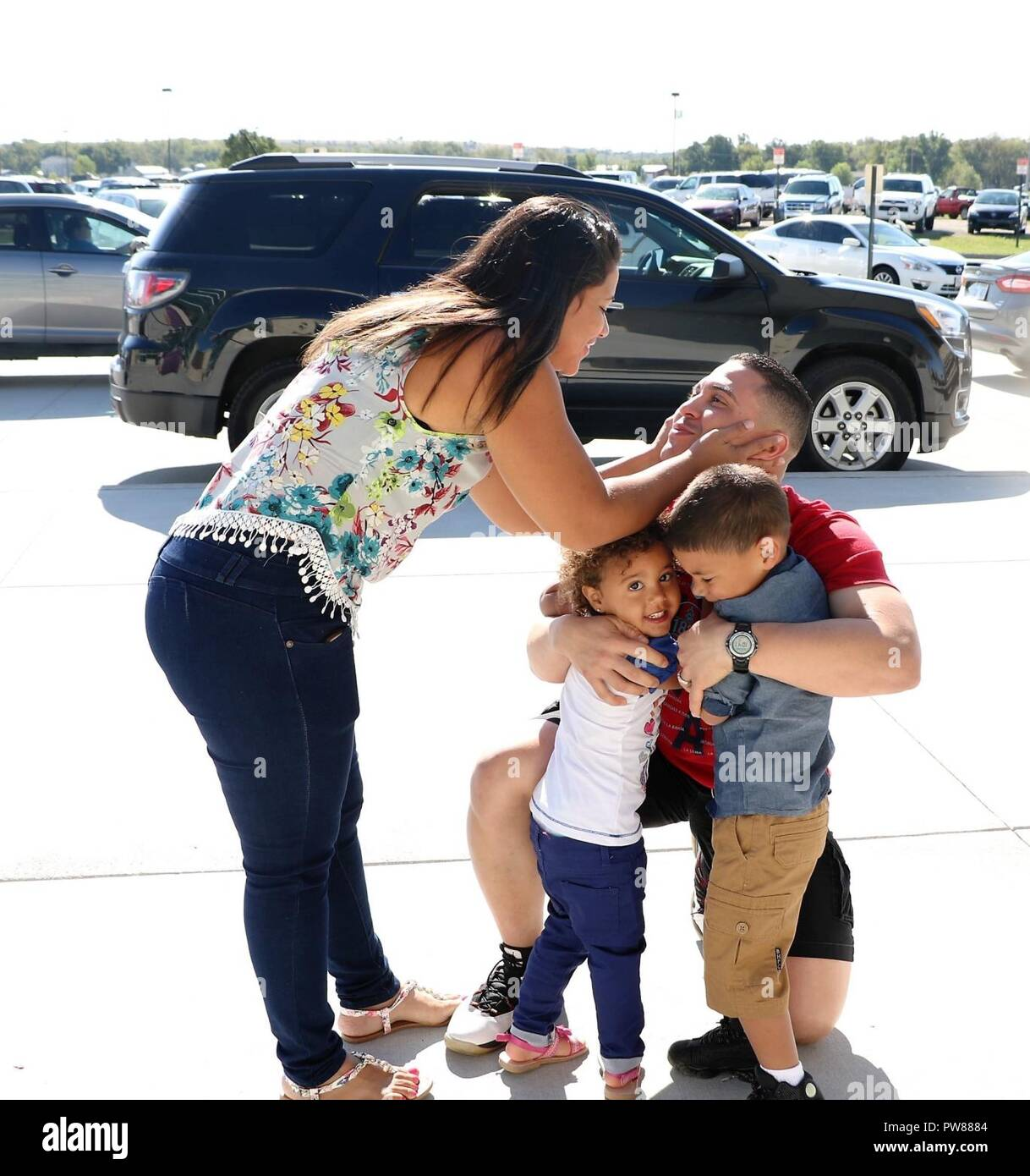 First Lieutenant Carlos Romero, disbursement officer with the 9th Financial Management Sustainment Unit, Special Troops Battalion, 1st Infantry Division Sustainment Brigade, reunites with his children, Adriel (center) and Thais Romero, and wife, Wendelyn Mendez-Maldonado, at Manhattan Regional Airport, Manhattan, Kansas, after returning from a nine-month deployment to Honduras on Sep. 28. Romero's family had also just returned from Puerto Rico shortly after Hurricane Maria devastated the island. (Sgt. 1st Class Victor Gardner, 1st Inf. Div. Sust. Bde. Public Affairs) - Stock Image