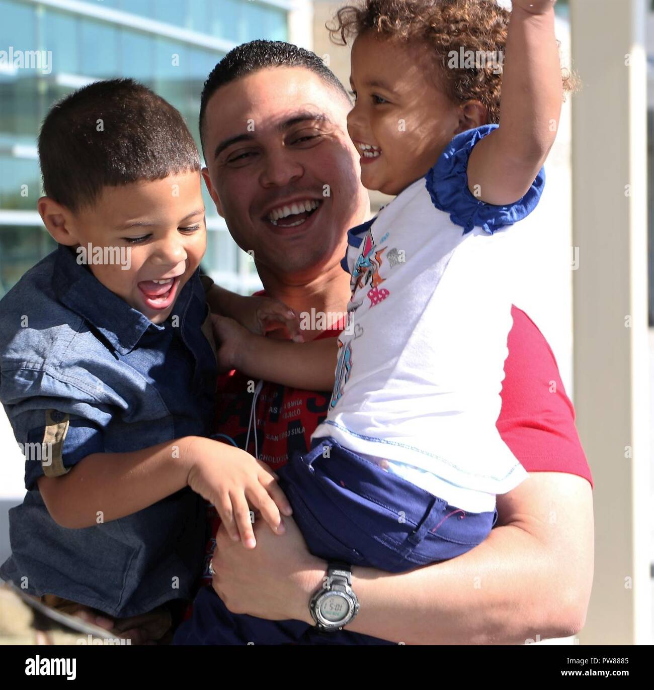 First Lieutenant Carlos Romero, disbursement officer with the 9th Financial Management Sustainment Unit, Special Troops Battalion, 1st Infantry Division Sustainment Brigade, holds his children Adriel (right) and Thais Romero at Manhattan Regional Airport, Manhattan, Kansas, after returning from a nine-month deployment to Honduras Sep. 28. Romero's family had also just returned from Puerto Rico shortly after Hurricane Maria devastated the island.  (Sgt. 1st Class Victor Gardner, 1st Inf. Div. Sust. Bde. Public Affairs) - Stock Image