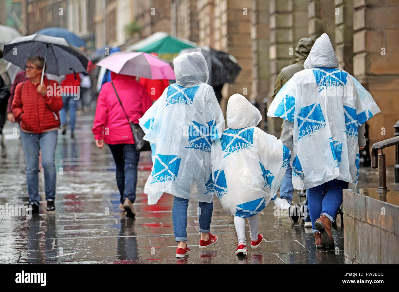 Tourists wearing emergency ponchos on Edinburgh's Royal Mile. - Stock Image