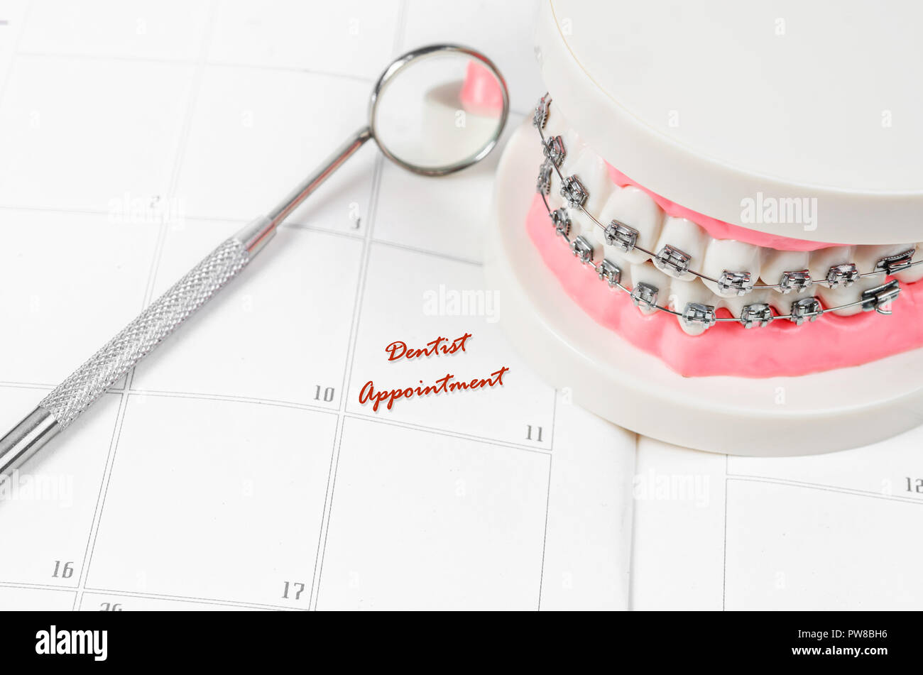 Tooth model with metal wire dental braces with dentist appointment on a calendar. Regular checkups are essential to oral health - Stock Image