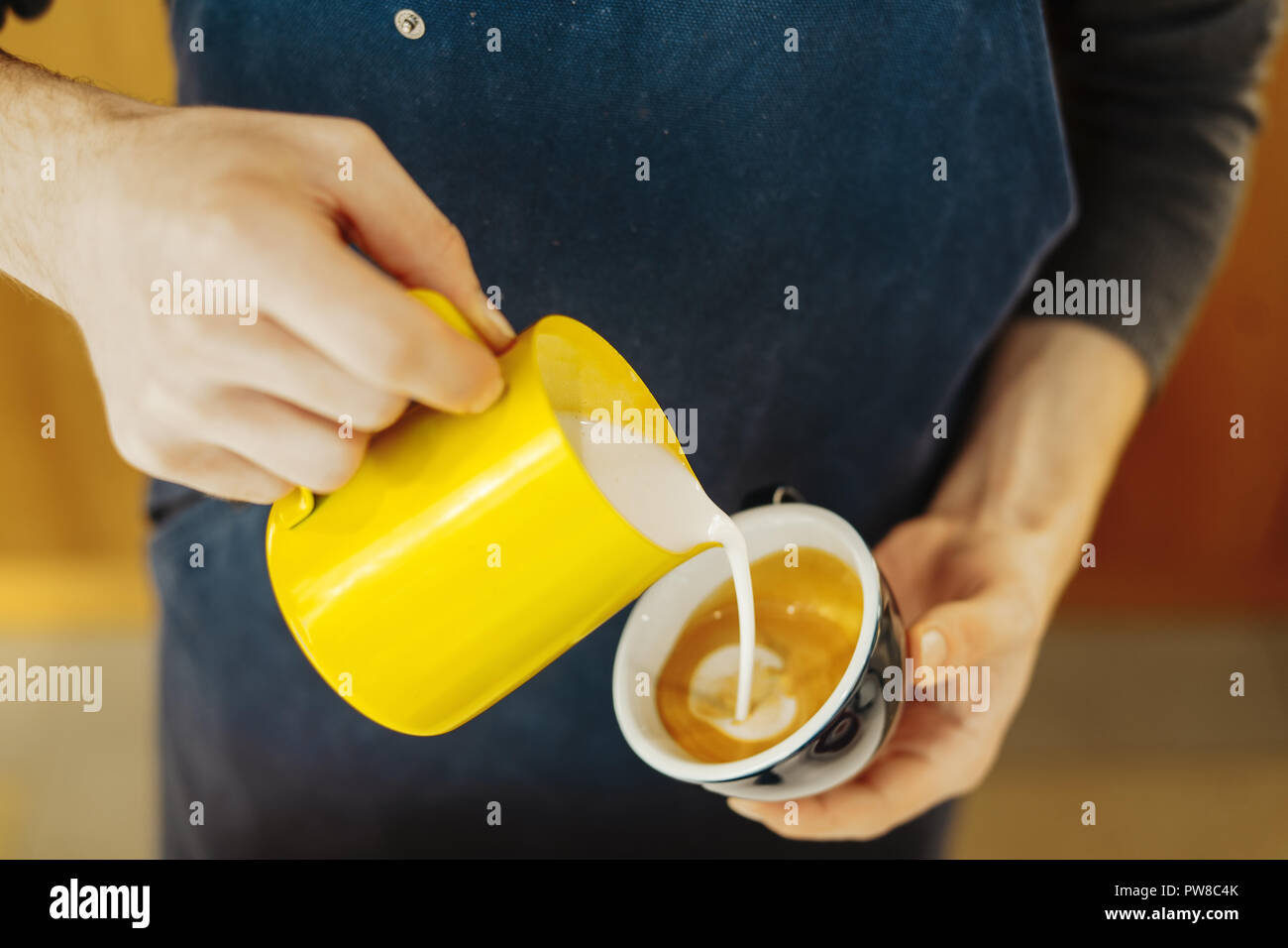 Close up of barista pouring steamed milk into coffee cup making latte art. - Stock Image