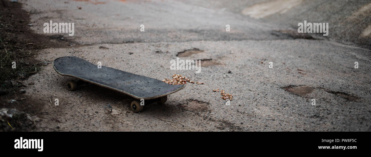 A skateboard on the ground at a skatepark. - Stock Image