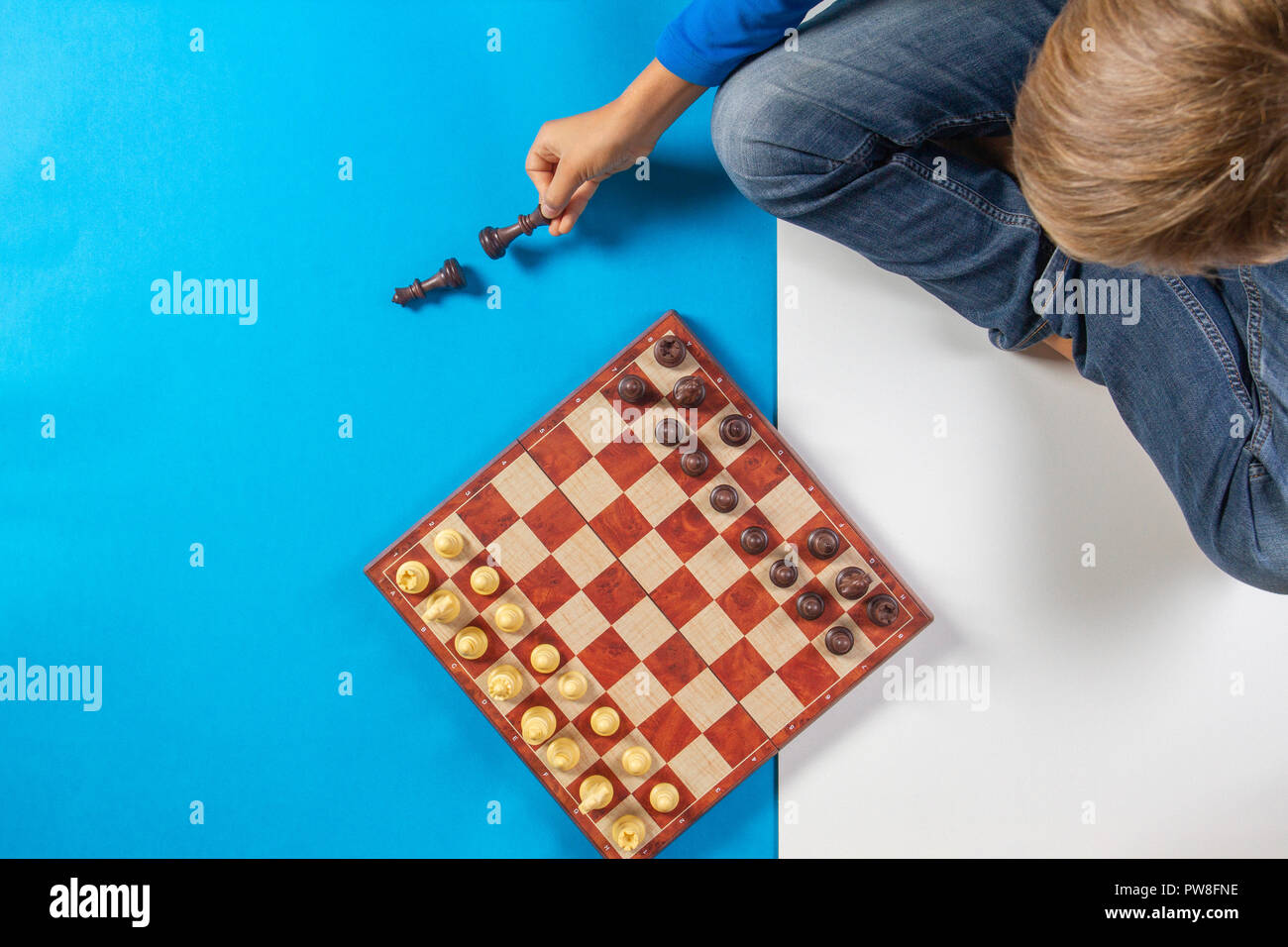 Kid sitting and learning to play chess game. Top view. Stock Photo