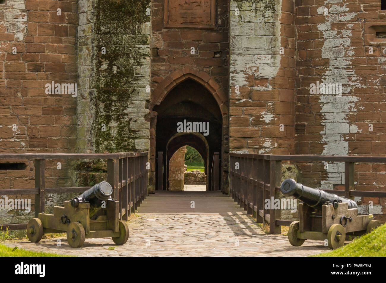 Shearington, Scotland, UK - June 18, 2012: Closeup of entrance gate into brown stone Caerlavarock Castle features bridge over moat and two sealed off  - Stock Image