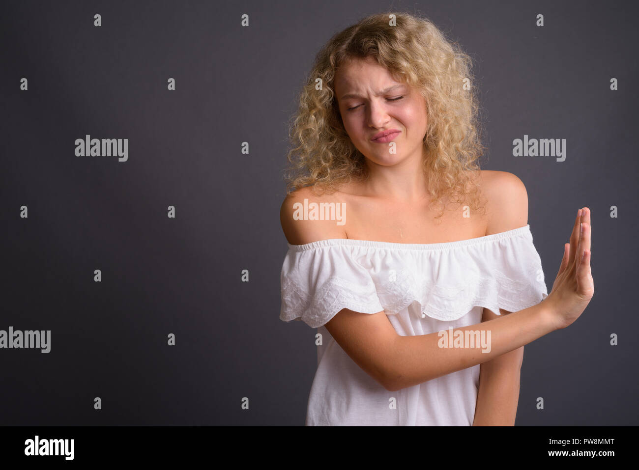 Young beautiful woman with blond curly hair against gray backgro - Stock Image