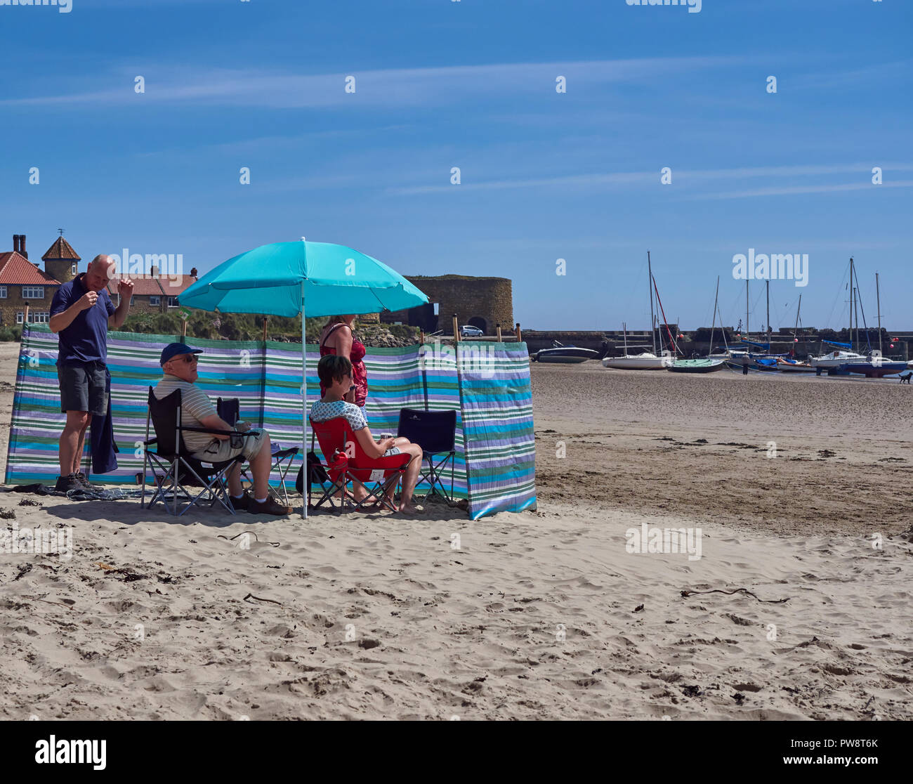 Holidaymakers sheltering from the wind by a wind Shelter on Beadnell Bay in Northumberland, England, UK. - Stock Image