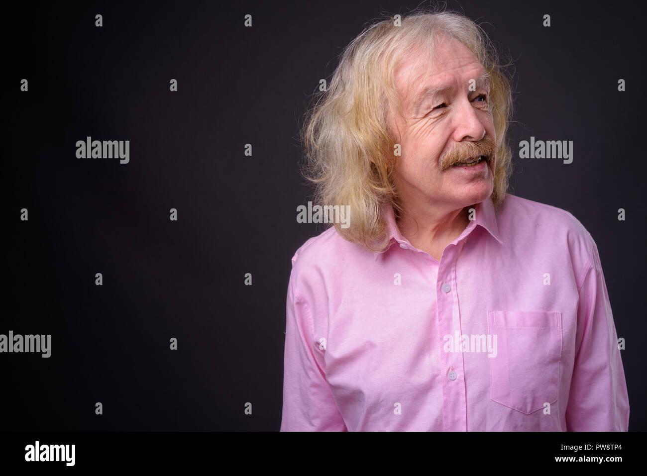 Senior businessman wearing pink shirt against gray background - Stock Image