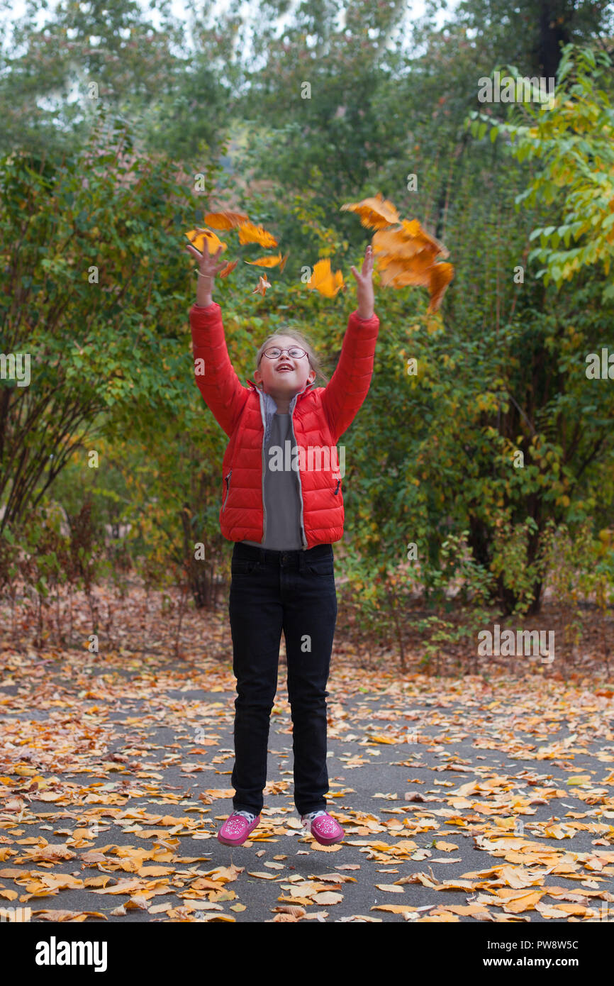 A girl with special needs jumping on a background of autumn forest throws up yellow leaves - Stock Image