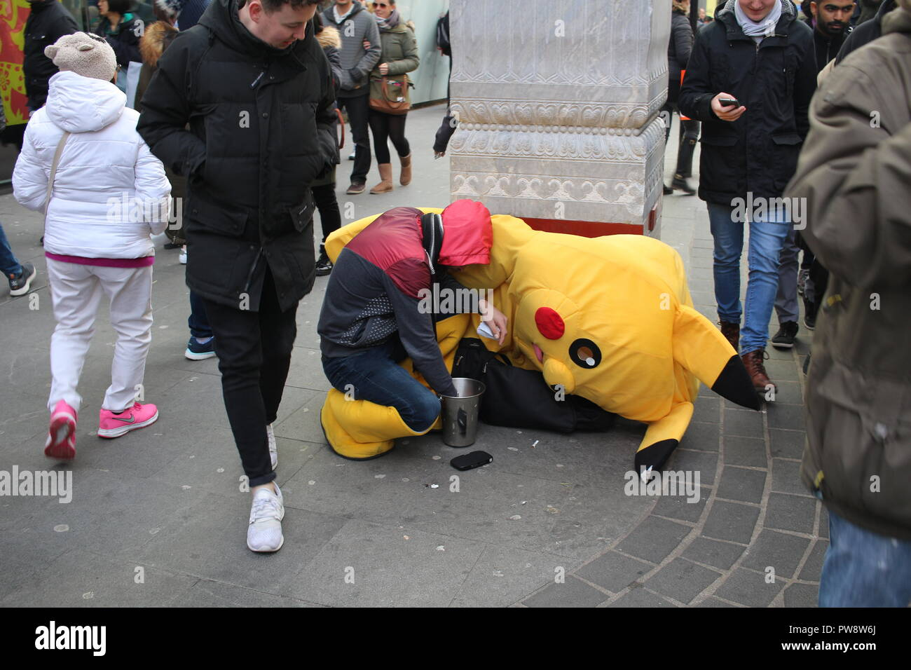 LONDON, UK - February 16, 2018: Exhausted street artist next to his fancy dress counting hard earned money, people walking and looking to him. Stock Photo