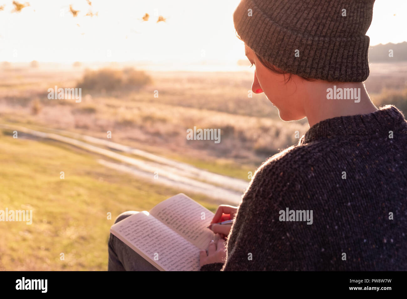 Writing a diary in beautiful nature. Woman facing evening sun takes notes into a notepad - Stock Image