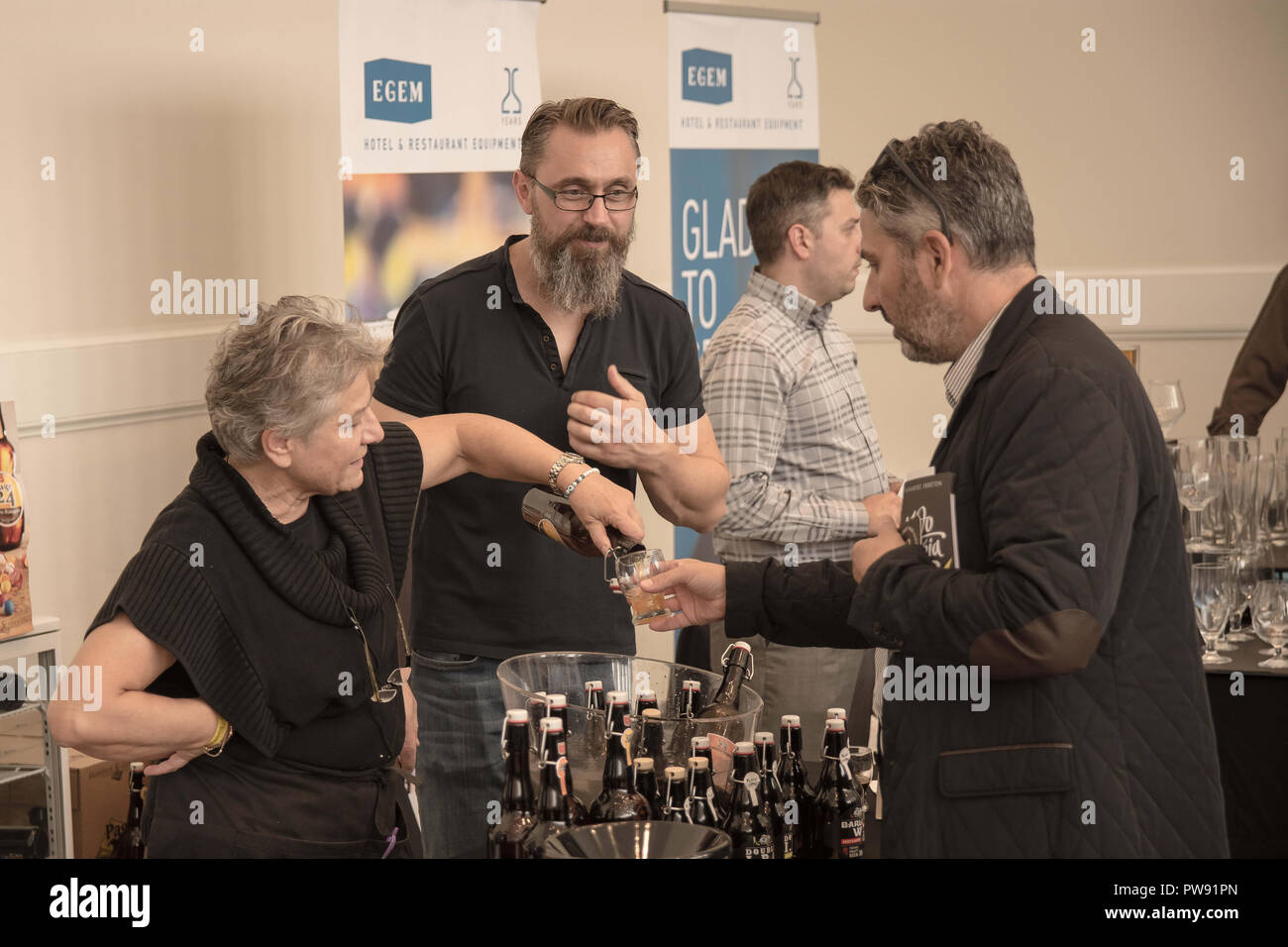 Athens, Greece. 13th Oct, 2018. A woman seen pouring beer into a glass from a bottle during the exhibition.The 5th Zythognosia Exhibition, people get a chance during the exhibition to taste multiple brews and premium beers from different brands and companies like Levante for Zante Lager, Asylum for Asylum saison, Mikonu for Mikonu Pale Ale, Deals for Fischer, Samichlaus and Cava di patsi for Flaros Session Ale in Zappeion Megaron in Athens. Credit: Nikolas Joao Kokovlis/SOPA Images/ZUMA Wire/Alamy Live News - Stock Image