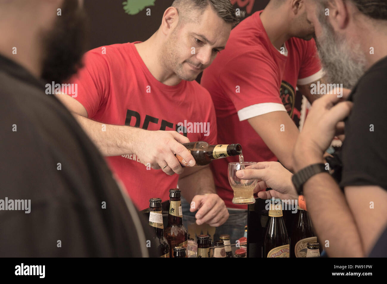 Athens, Greece. 13th Oct, 2018. A man seen pouring beer into a glass from a bottle during the exhibition.The 5th Zythognosia Exhibition, people get a chance during the exhibition to taste multiple brews and premium beers from different brands and companies like Levante for Zante Lager, Asylum for Asylum saison, Mikonu for Mikonu Pale Ale, Deals for Fischer, Samichlaus and Cava di patsi for Flaros Session Ale in Zappeion Megaron in Athens. Credit: Nikolas Joao Kokovlis/SOPA Images/ZUMA Wire/Alamy Live News - Stock Image
