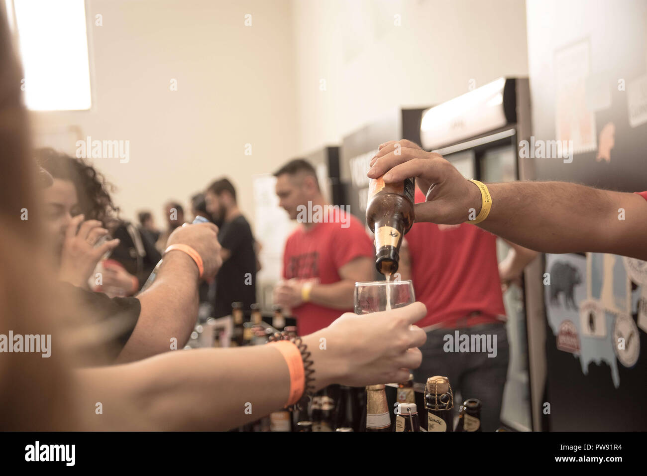Athens, Greece. 13th Oct, 2018. A beer seen being poured into a glass from a bottle during the exhibition.The 5th Zythognosia Exhibition, people get a chance during the exhibition to taste multiple brews and premium beers from different brands and companies like Levante for Zante Lager, Asylum for Asylum saison, Mikonu for Mikonu Pale Ale, Deals for Fischer, Samichlaus and Cava di patsi for Flaros Session Ale in Zappeion Megaron in Athens. Credit: Nikolas Joao Kokovlis/SOPA Images/ZUMA Wire/Alamy Live News - Stock Image