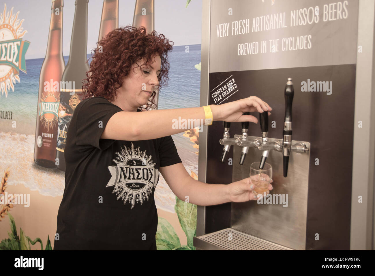 Athens, Greece. 13th Oct, 2018. A woman seen pouring beer into a glass during the exhibition.The 5th Zythognosia Exhibition, people get a chance during the exhibition to taste multiple brews and premium beers from different brands and companies like Levante for Zante Lager, Asylum for Asylum saison, Mikonu for Mikonu Pale Ale, Deals for Fischer, Samichlaus and Cava di patsi for Flaros Session Ale in Zappeion Megaron in Athens. Credit: Nikolas Joao Kokovlis/SOPA Images/ZUMA Wire/Alamy Live News - Stock Image