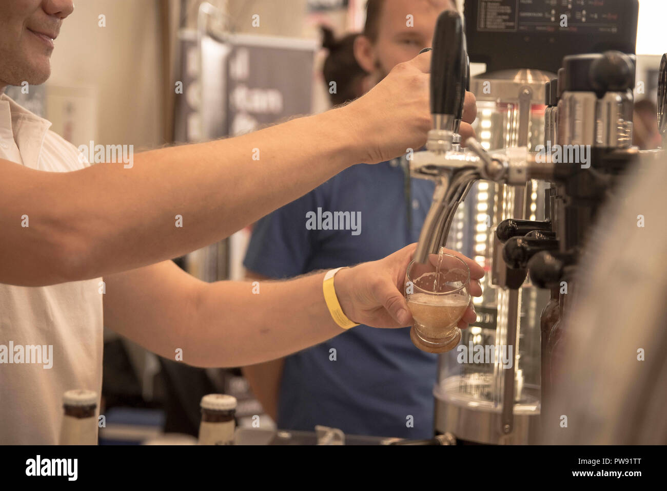 Athens, Greece. 13th Oct, 2018. A man seen pouring beer into a glass during the exhibition.The 5th Zythognosia Exhibition, people get a chance during the exhibition to taste multiple brews and premium beers from different brands and companies like Levante for Zante Lager, Asylum for Asylum saison, Mikonu for Mikonu Pale Ale, Deals for Fischer, Samichlaus and Cava di patsi for Flaros Session Ale in Zappeion Megaron in Athens. Credit: Nikolas Joao Kokovlis/SOPA Images/ZUMA Wire/Alamy Live News - Stock Image