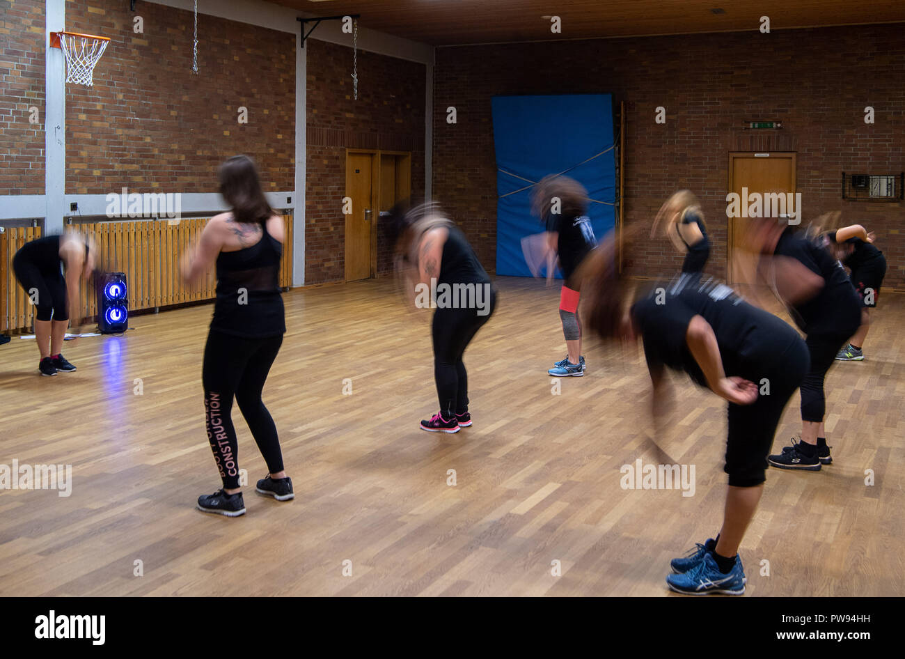 11 October 2018, Baden-Wuerttemberg, Ludwigsburg: 11 October 2018, Germany, Ludwigsburg: Participants headbanging during a Metalza hour at the Athletlik-Sportverein. Metalza is a dance workshop with metal music. (to dpa 'Headbanging as fitness program - Workout for metal fans' from 14.10.2018) Photo: Sebastian Gollnow/dpa - Stock Image