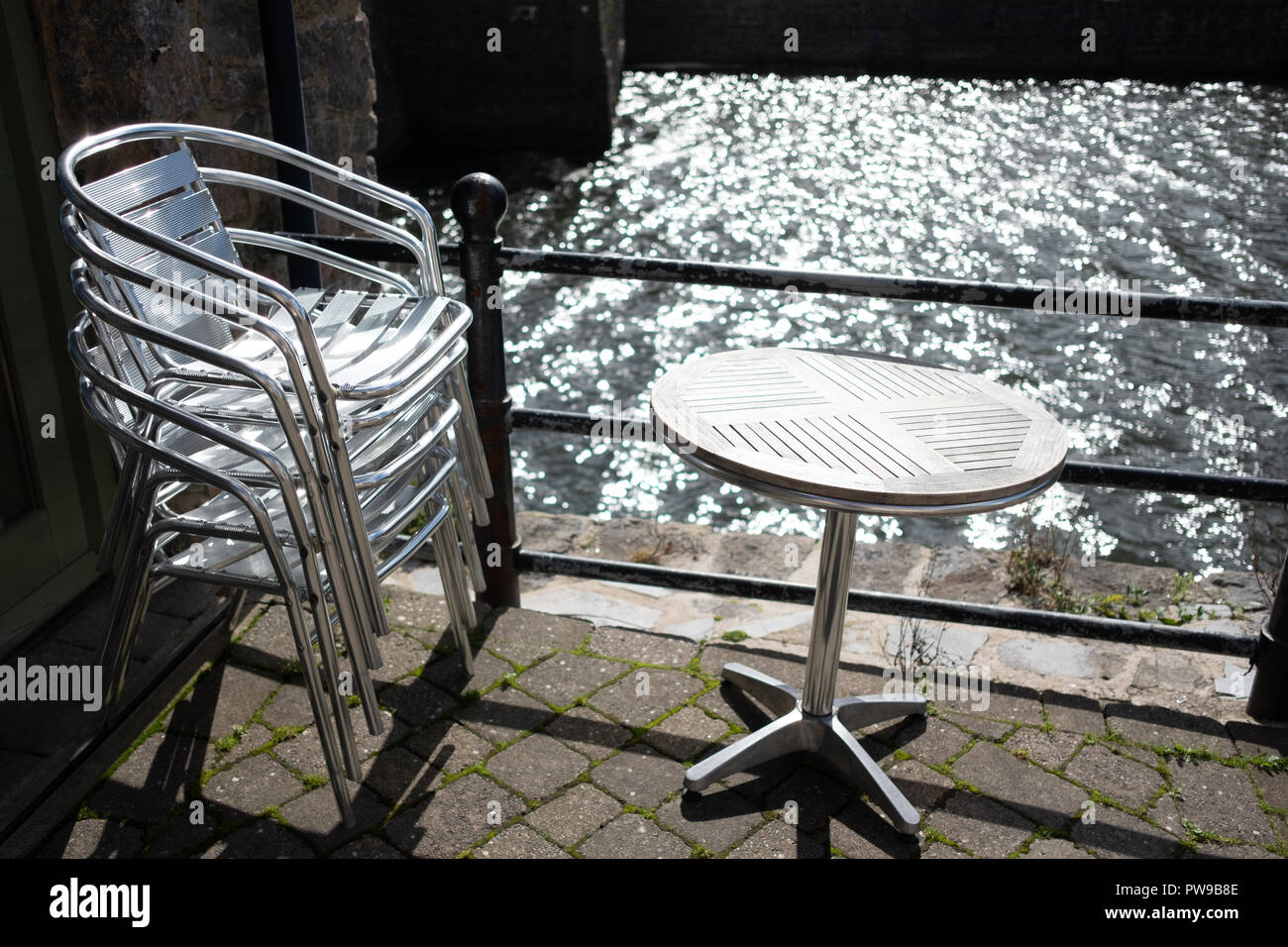Alu Design Vaison La Romaine stacked metal chairs and table outside a cafe on a sunny day