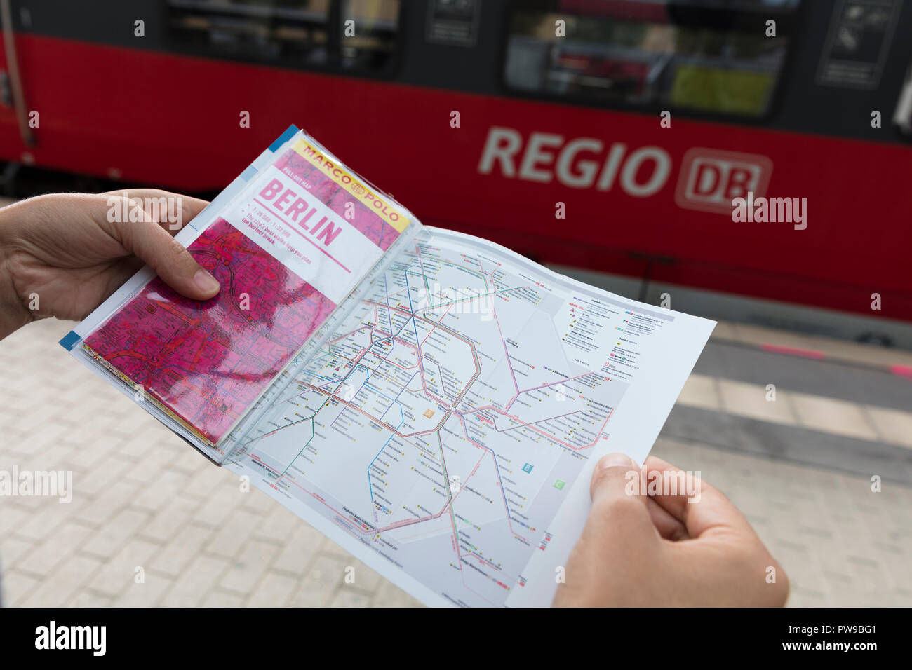 Potsdam, Berlin, Germany: 18th August 2018: Tourist looking at Marco Polo Guide and Public transport map Stock Photo