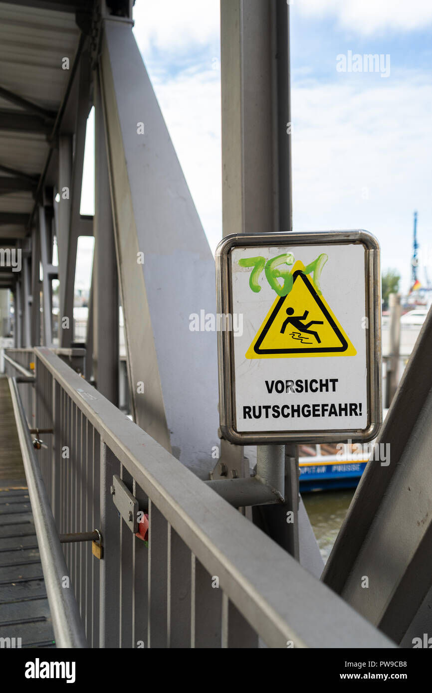 Warning sign on a pedestrian bridge not to Slip and Fall with scrawled green graffiti lettering - Stock Image