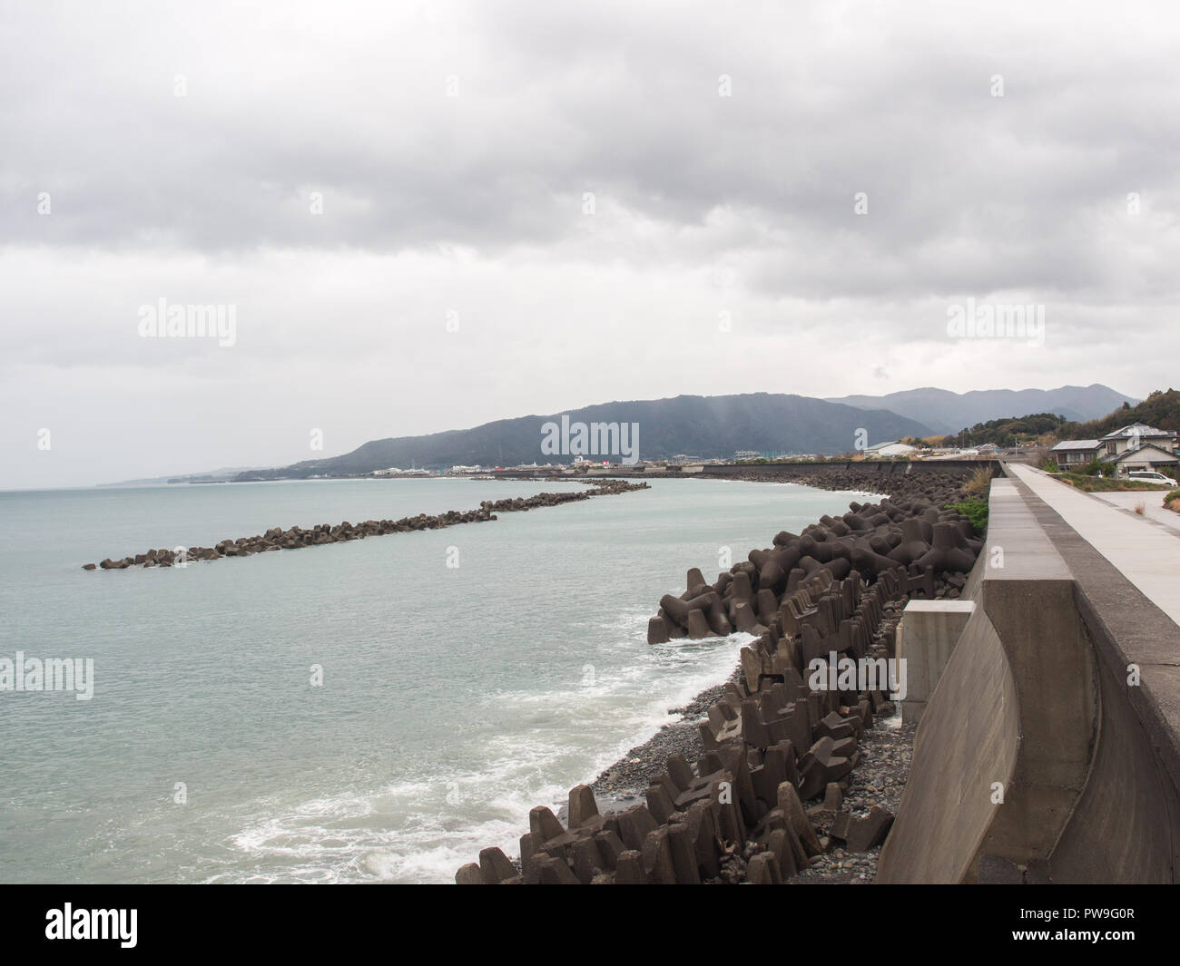 Tetrapods lining concrete sea wall, the curve of the coast, a tetrapod reef off-shore, coast protection, a town built along the shore, Aki, Kochi, Shi - Stock Image