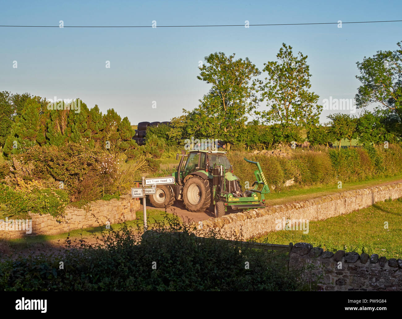 A Tractor turns in to a Farmhouse Entrance after a long Summers day at work in Northumberland in England, UK. - Stock Image