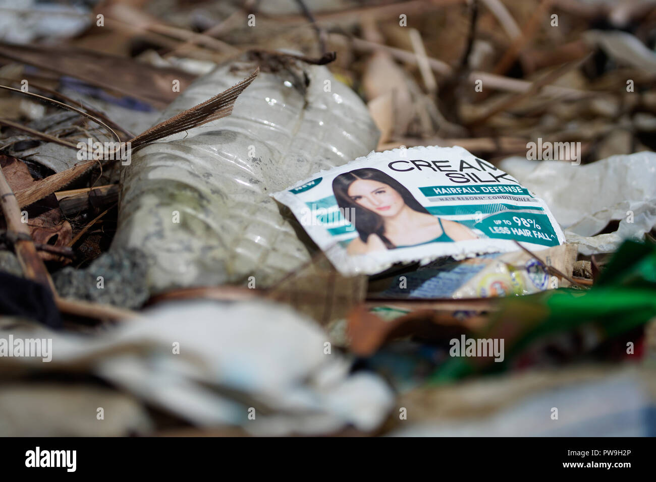 Single use plastic sachets discarded directly into the environment - regarded as one of the main plastic pollutants within South East Asia. - Stock Image