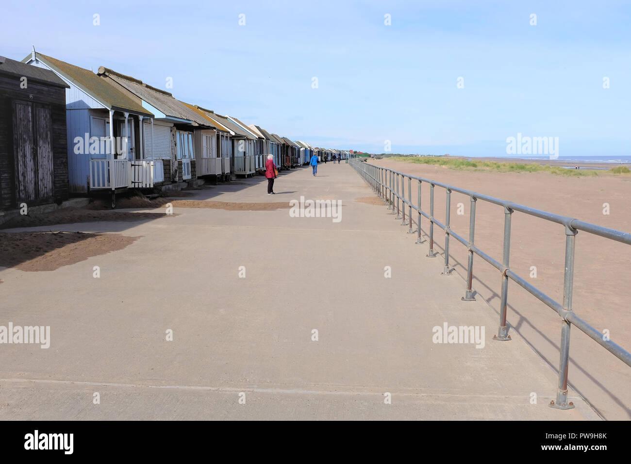 Sandilands, Lincolnshire, UK. October 07, 2018.  Holidaymakers enjoying a long line of various sized beach huts on the promenade at Sandilands near Su - Stock Image