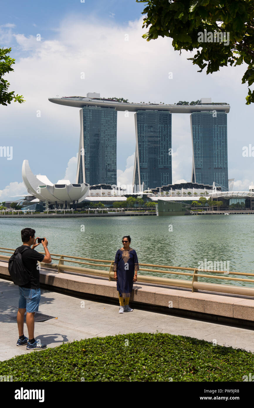 Indian tourist posing for picture outside Marina Bay Sands architecture. - Stock Image