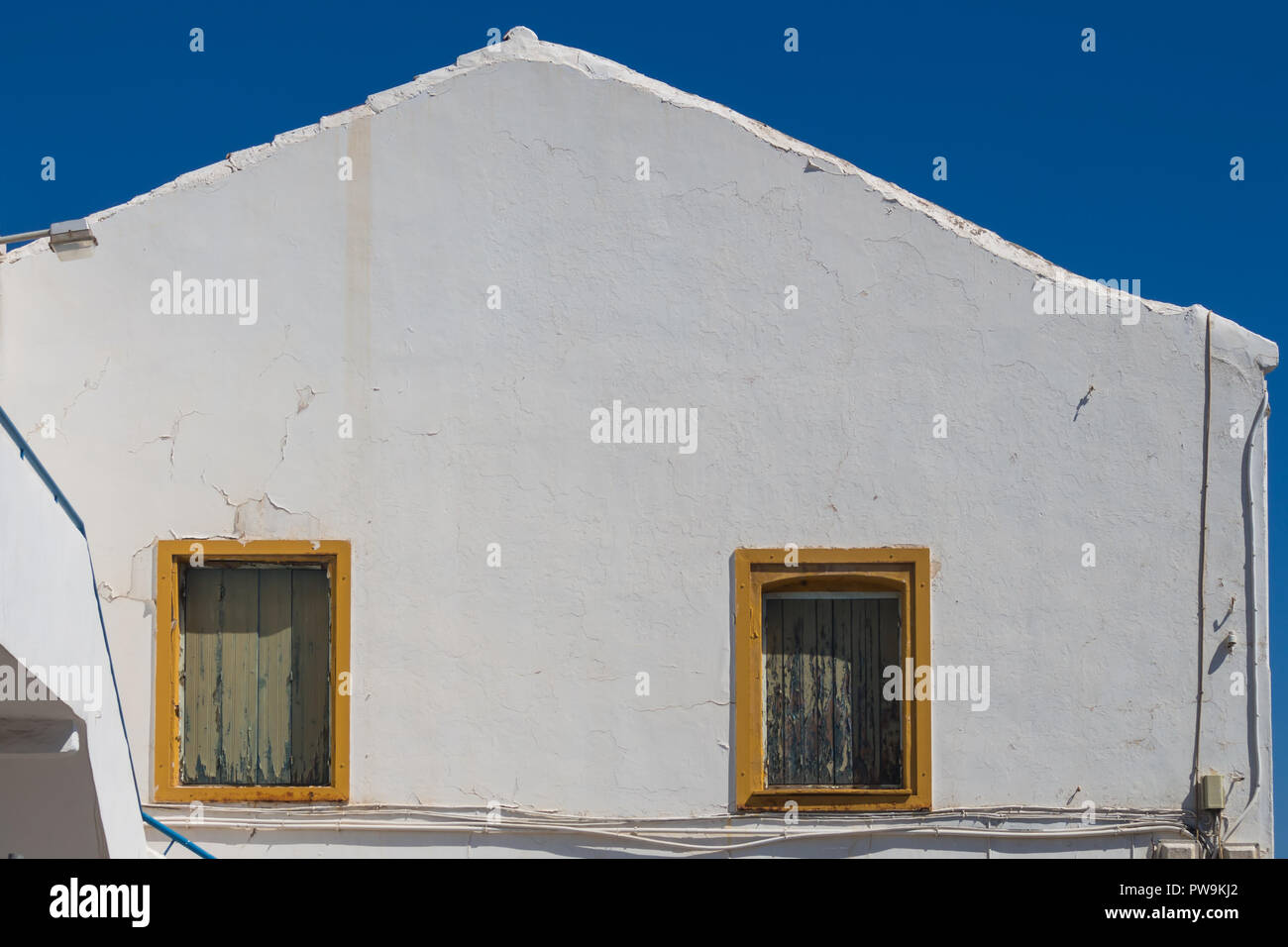 Building with a bright white older facade. Two windows with yellow ...
