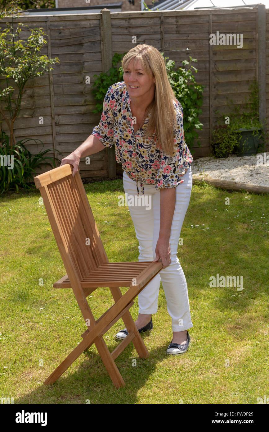 Woman opening a folding garden teak chair. - Stock Image