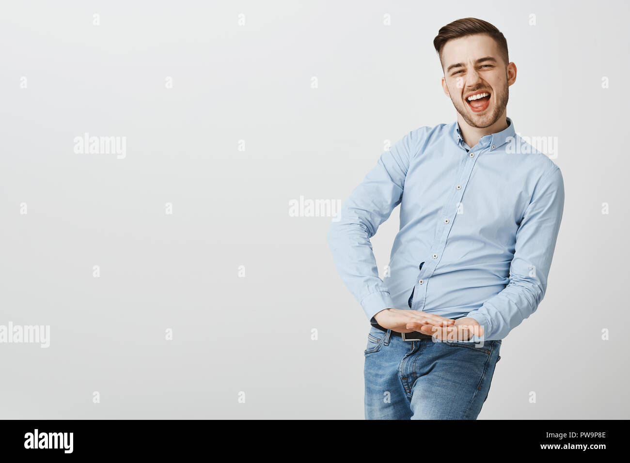 Guy ready to waste money being rich and carefree. Portrait of joyful good-looking young male entrepreneur in formal blue shirt saying yeah while throwing cash in air being successful businessman - Stock Image