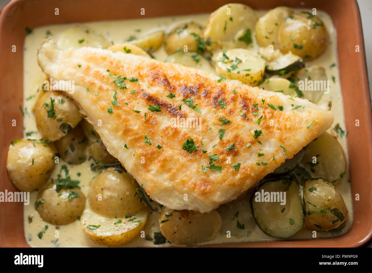A pollack fillet, Pollachius pollachius, that has been dipped in flour and fried. It is served on a bed of boiled potatoes, fried courgettes with lemo - Stock Image