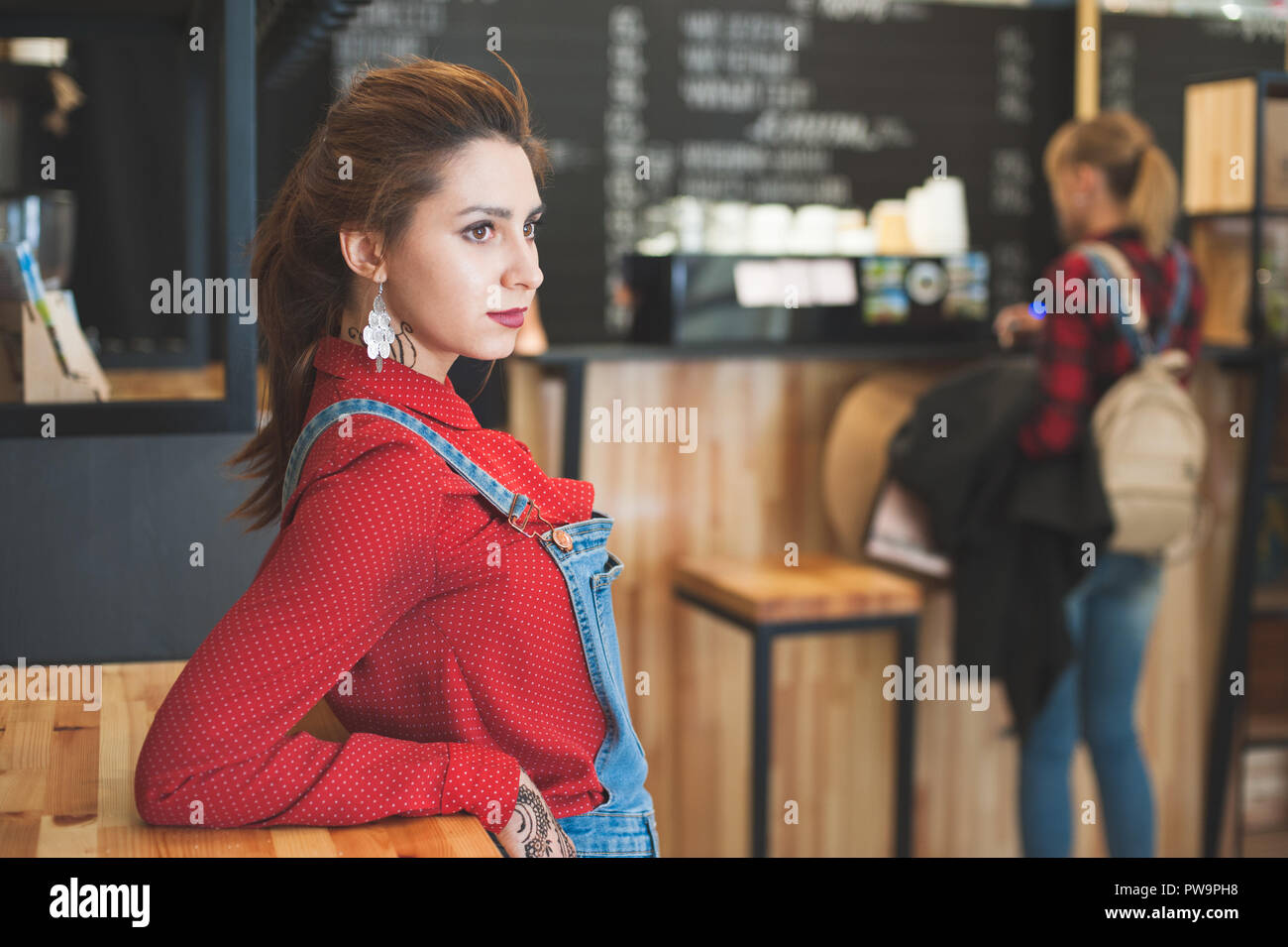 two young caucasian girls wearing jeans in modern design coffeehouse during coffee break - Stock Image