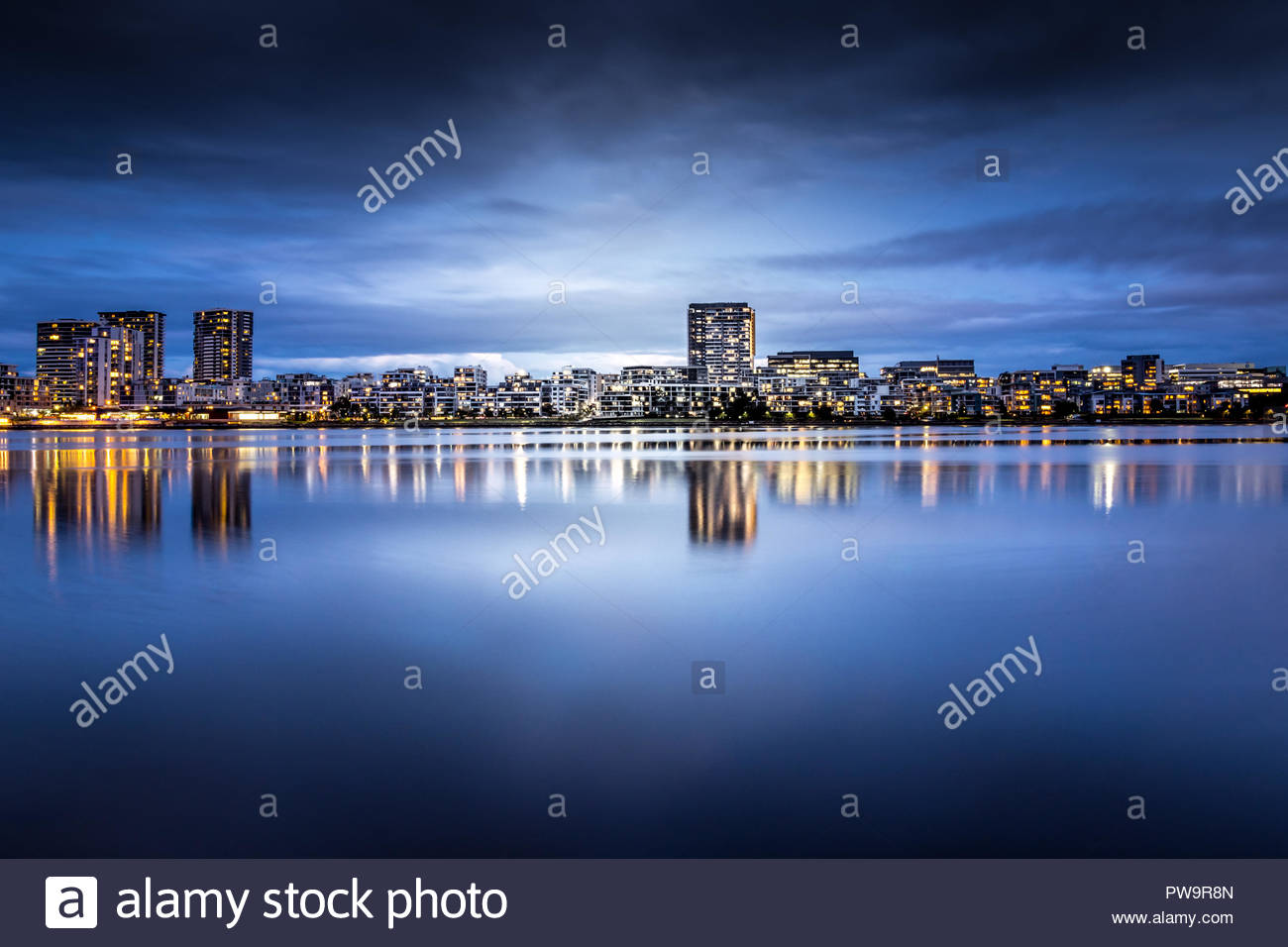 Modern apartments in a medium density suburb along the river. Reflections in the water. Dusk sky. Long exposure - Stock Image