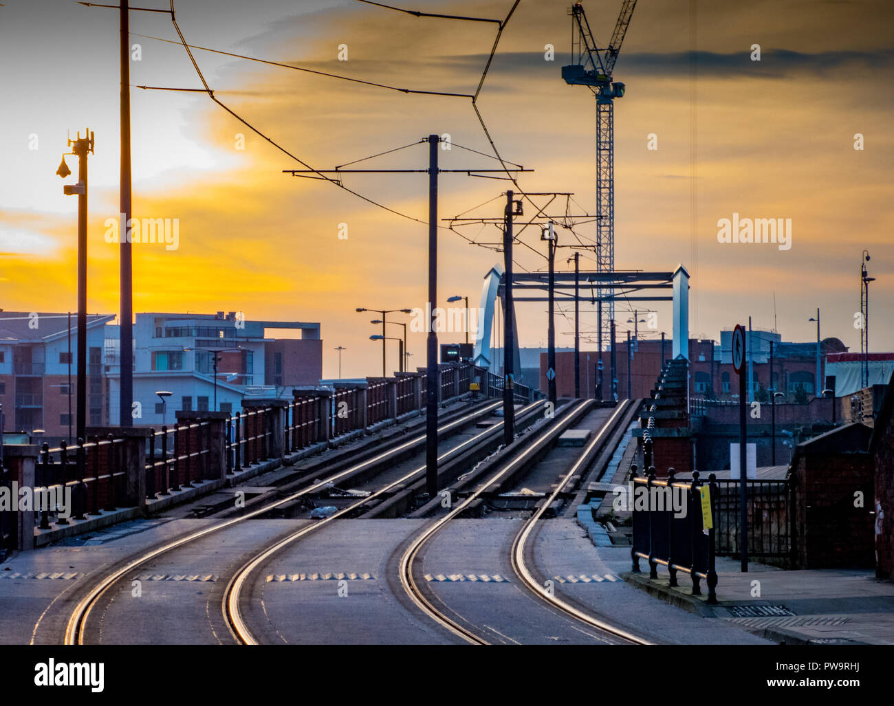 Tram and tramlines in central Manchester, UK, with setting sun and clouds - Stock Image