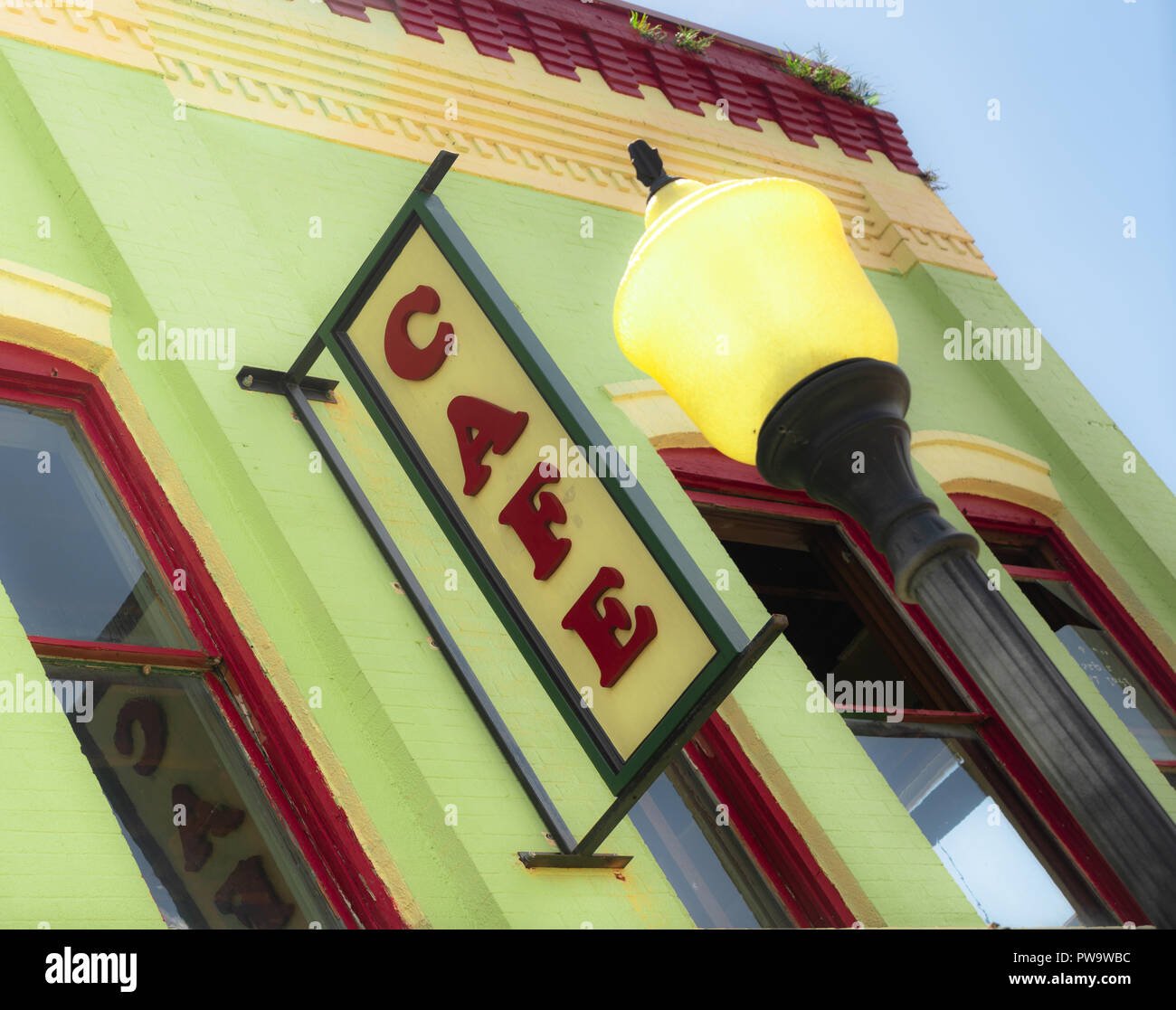 Tight crop with blue sky and clouds building wall cafe sign slanted view yellow lamppost - Stock Image
