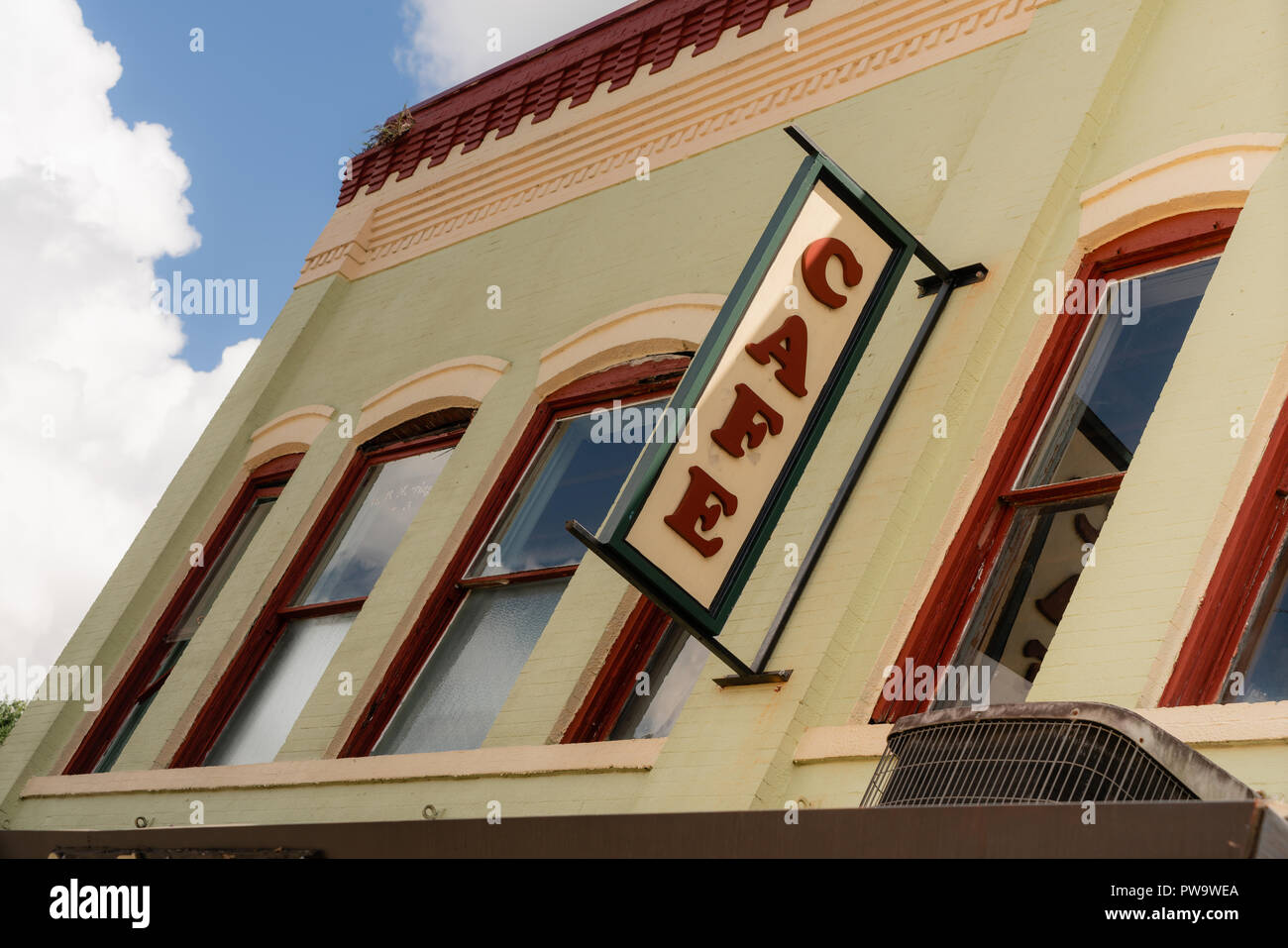 Tight crop with blue sky and clouds building wall cafe sign slanted view - Stock Image