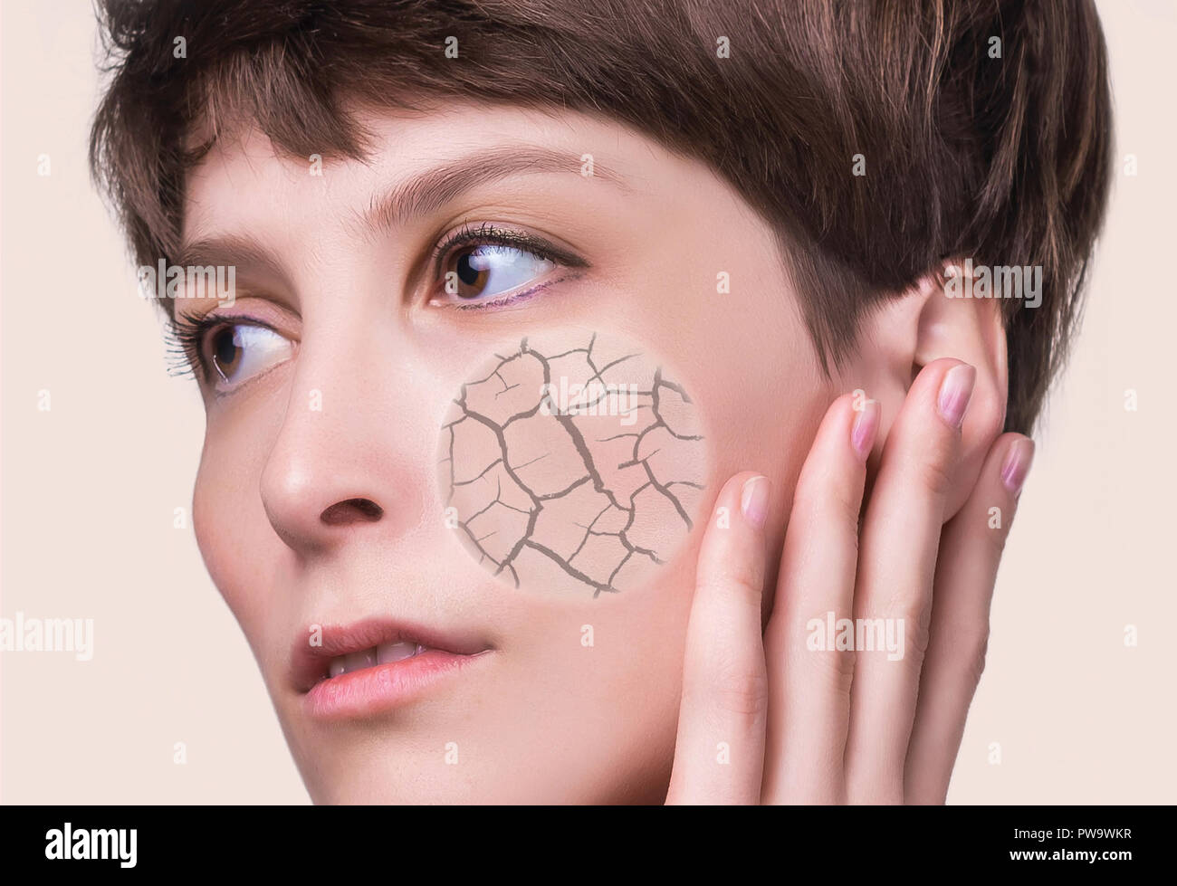 Woman face covered with cracked earth texture- symbol of dry skin Stock Photo