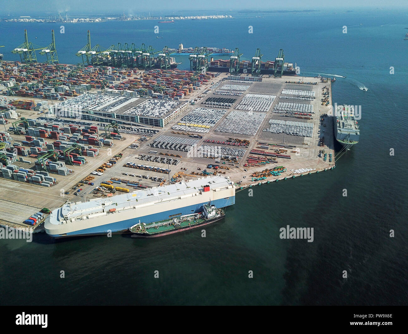 Drone aerial view of vehicles, container ships and car carriers at West Coast Park, Singapore. - Stock Image
