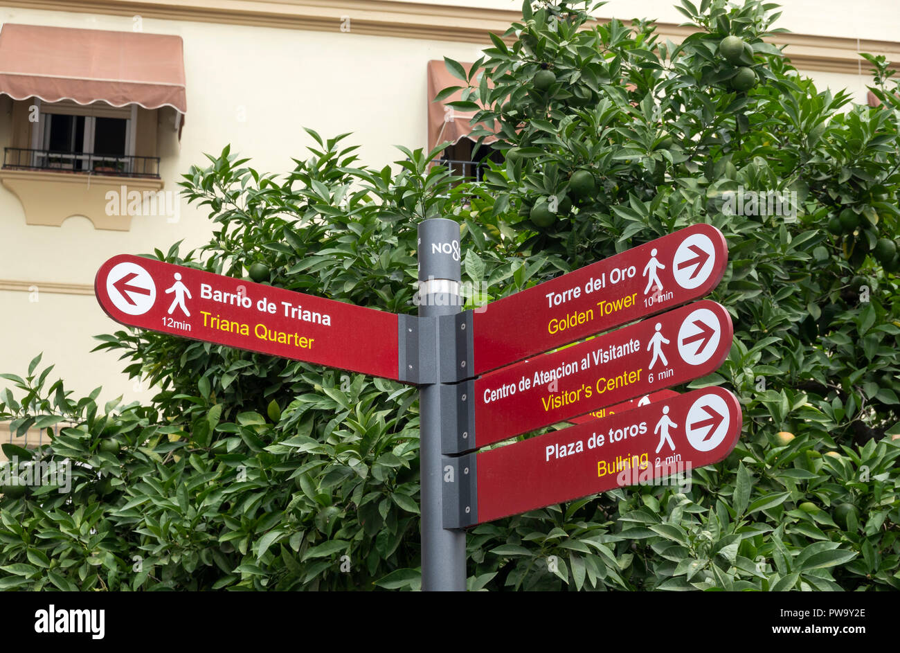 Directional walking signs with minutes on a street in Seville, Spain - Stock Image