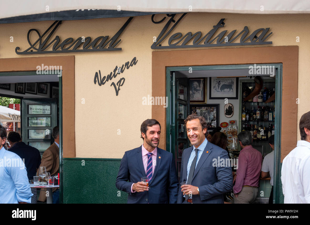 Two Spanish businessmen in suits and ties sharing a drink and a talk outside the Arenal Ventura bar in Seville, Andalusia, Spain - Stock Image