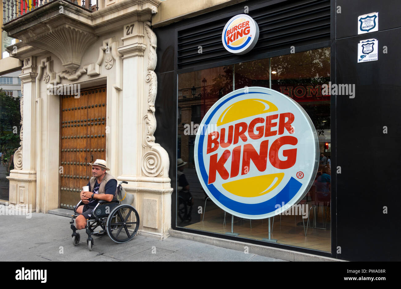 Legless man in a wheelchair solicits money in a cup outside a Burger King in Seville, Spain - Stock Image