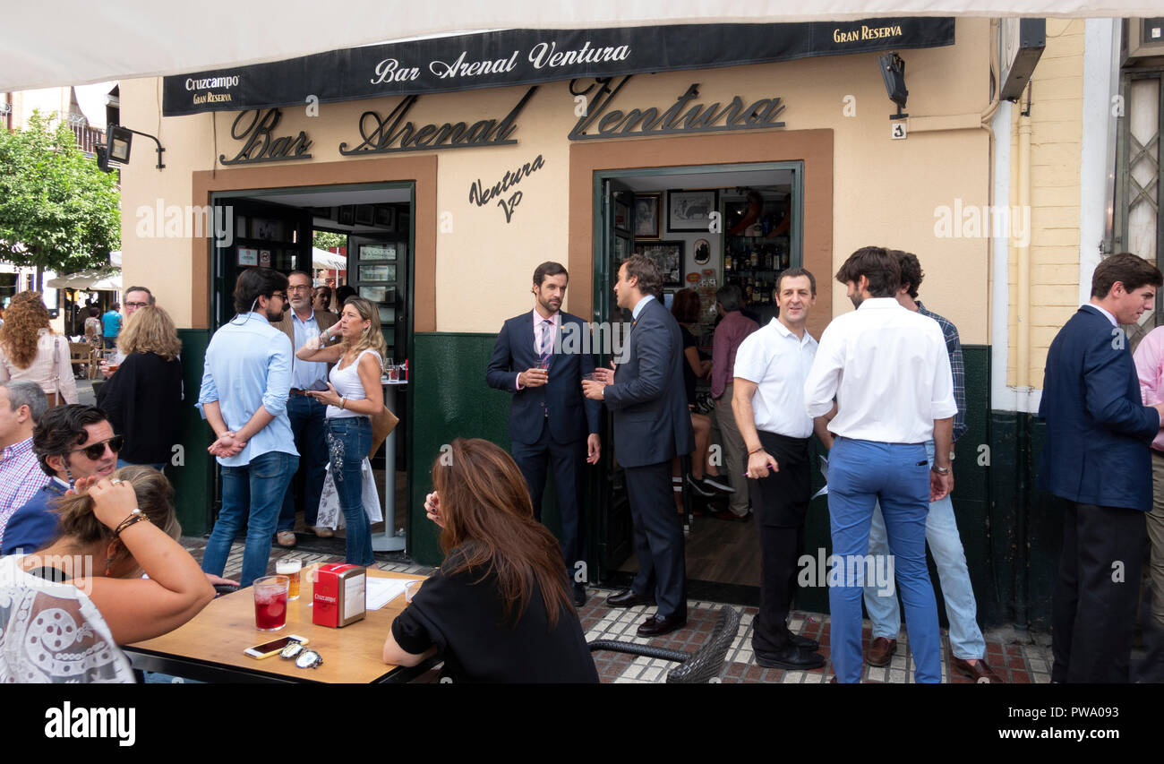 Two young Spanish businessmen in suits and ties sharing a drink and a talk outside the Arenal Ventura bar in Seville, Andalusia, Spain - Stock Image
