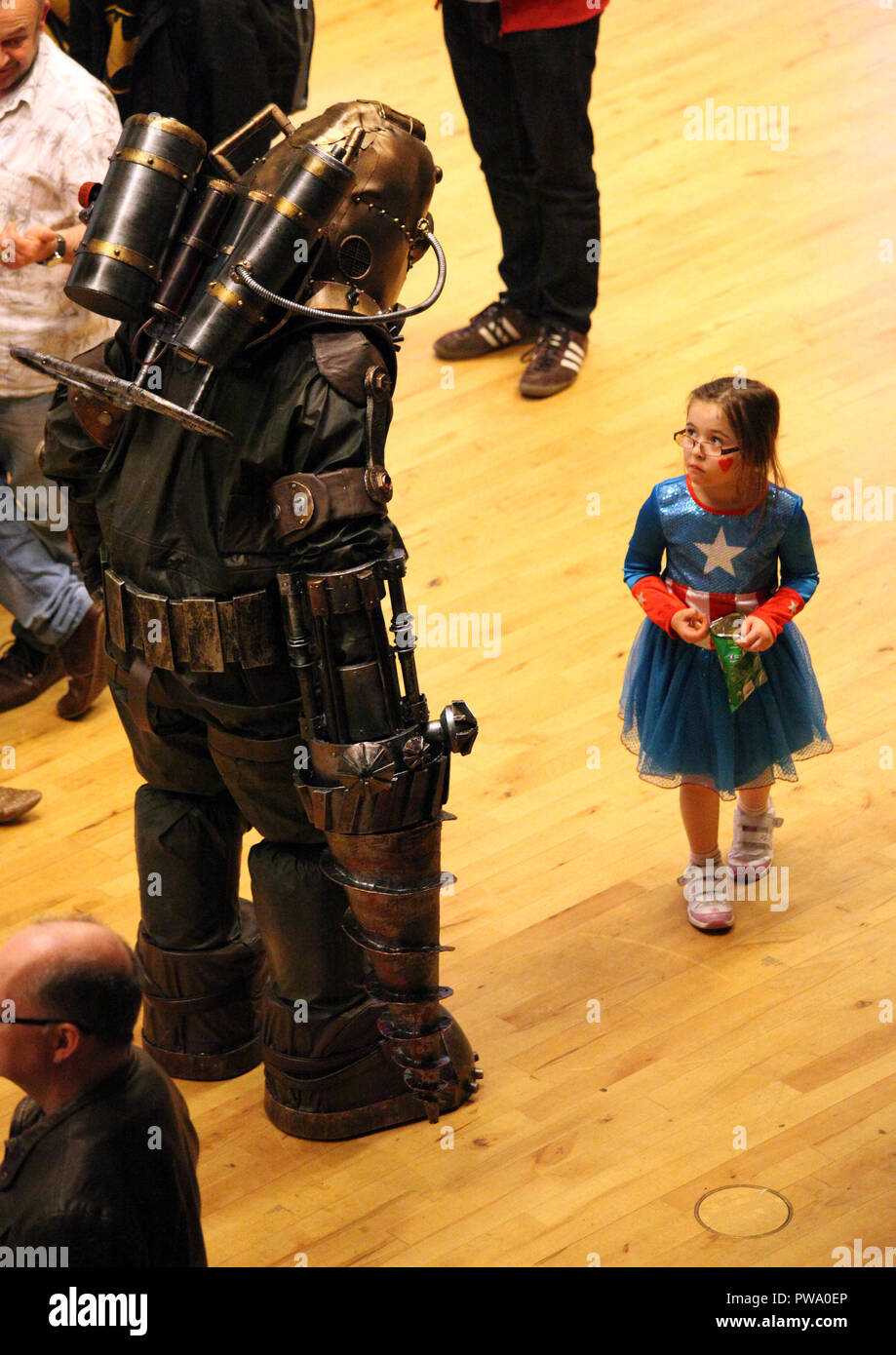 Sci-fi convention with robot and small girl super hero - Stock Image