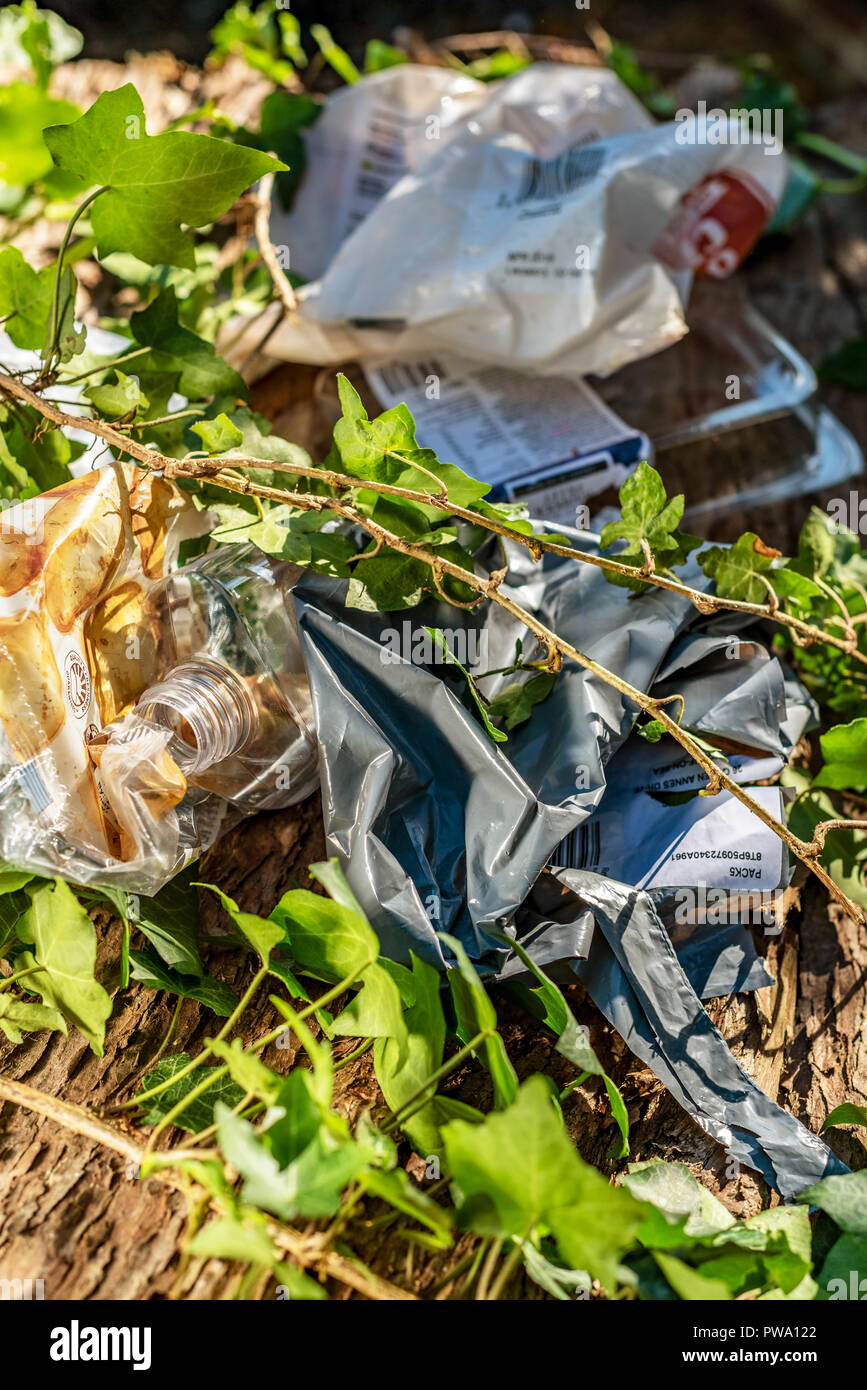 Plastic waste abandoned in the countryside. Environment pollution with rubbish overgrown by vegetation. Stock Photo