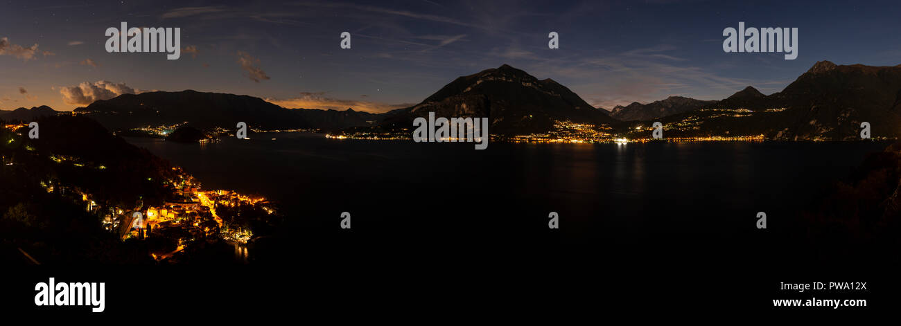 Panorama overlooking Lake Como and surrounding mountains in northern Italy at night - Stock Image
