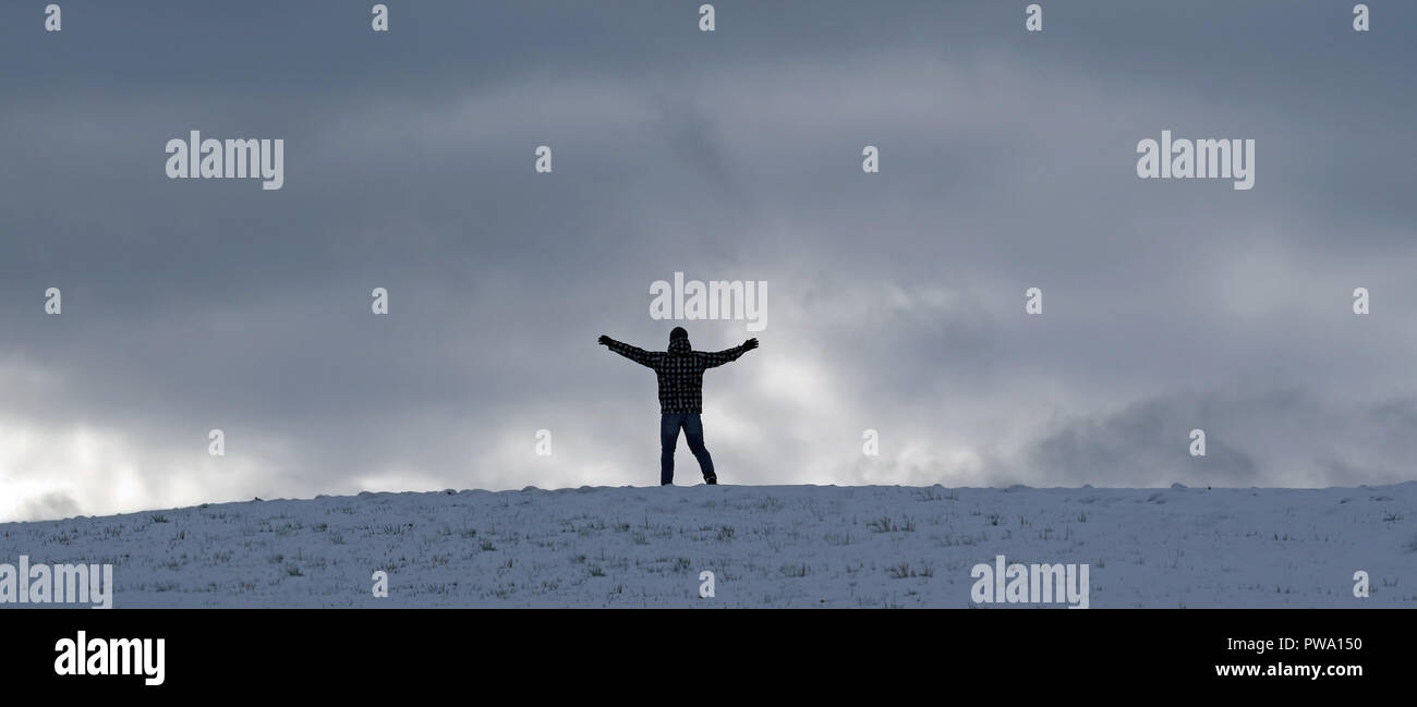 In the winter, a man stands in front of a cloudy sky and feels free - Stock Image